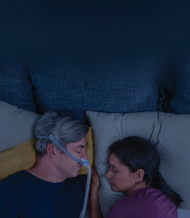 man-sleeping-with-AirFit-N30-CPAP-mask-close-to-his-wife-resmed-mobile