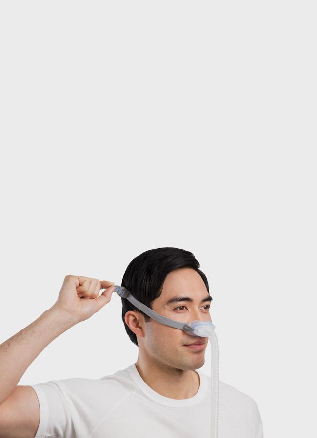 sleep-apnoea-patient-adjusting-AirFit-N30-nasal-cradle-mask-resmed-mobile